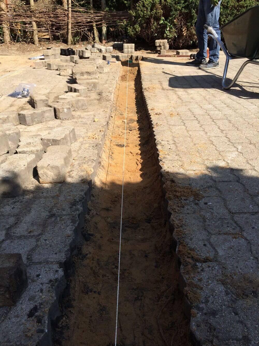 Pflastersteine hochgenommen um die Entwässerungsrinne einzubauen