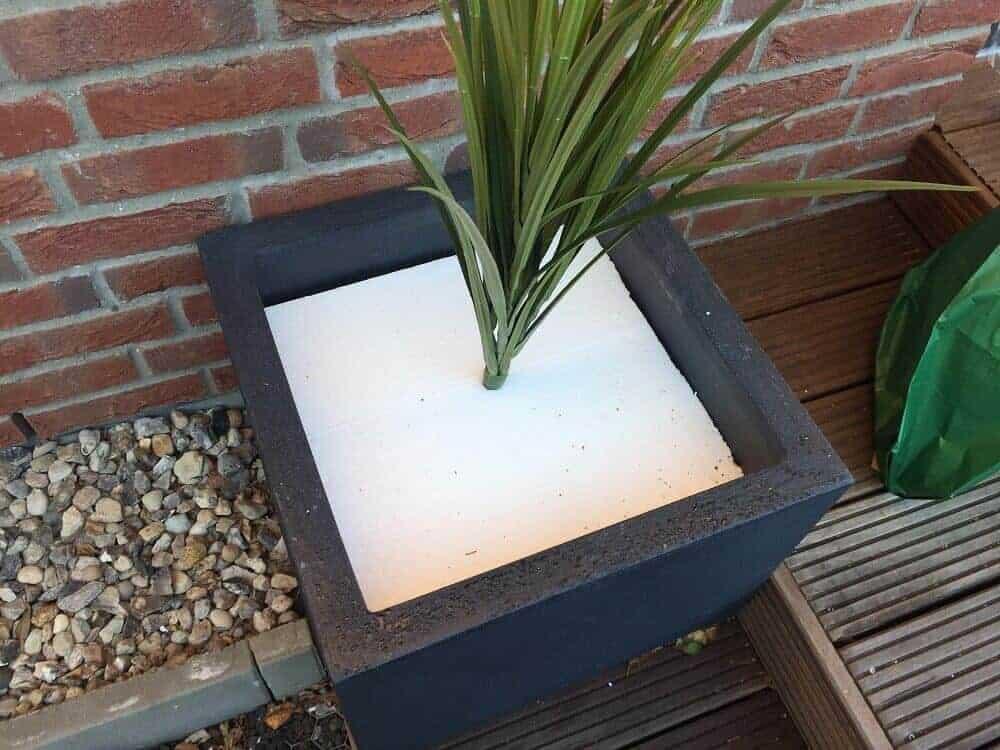 Die Kunstpflanze wird einfach im Styropor vom Pflanzkübel versenkt