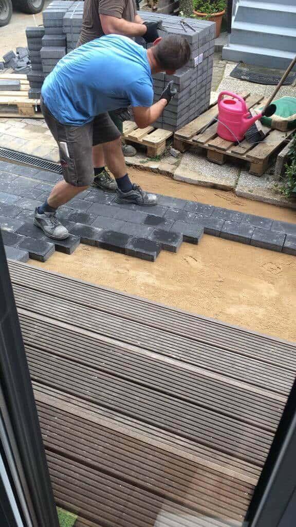 Die Pflastersteine vor der Eingangstreppe werden verlegt