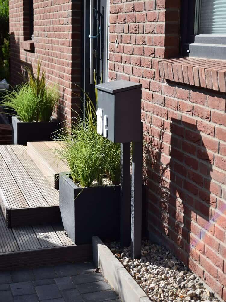 eingangsbereich mit pflanzkübel kunstpflanzen und kies gestalten