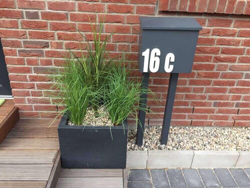 Hauseingang verschönert mit Kunstpflanzen und Pflanzkübel aus Kunststoff