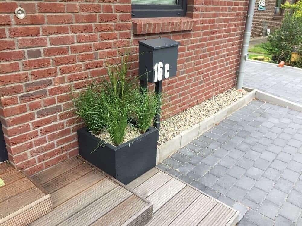 Pflanzkübel mit Kunstpflanzen vor der Haustür