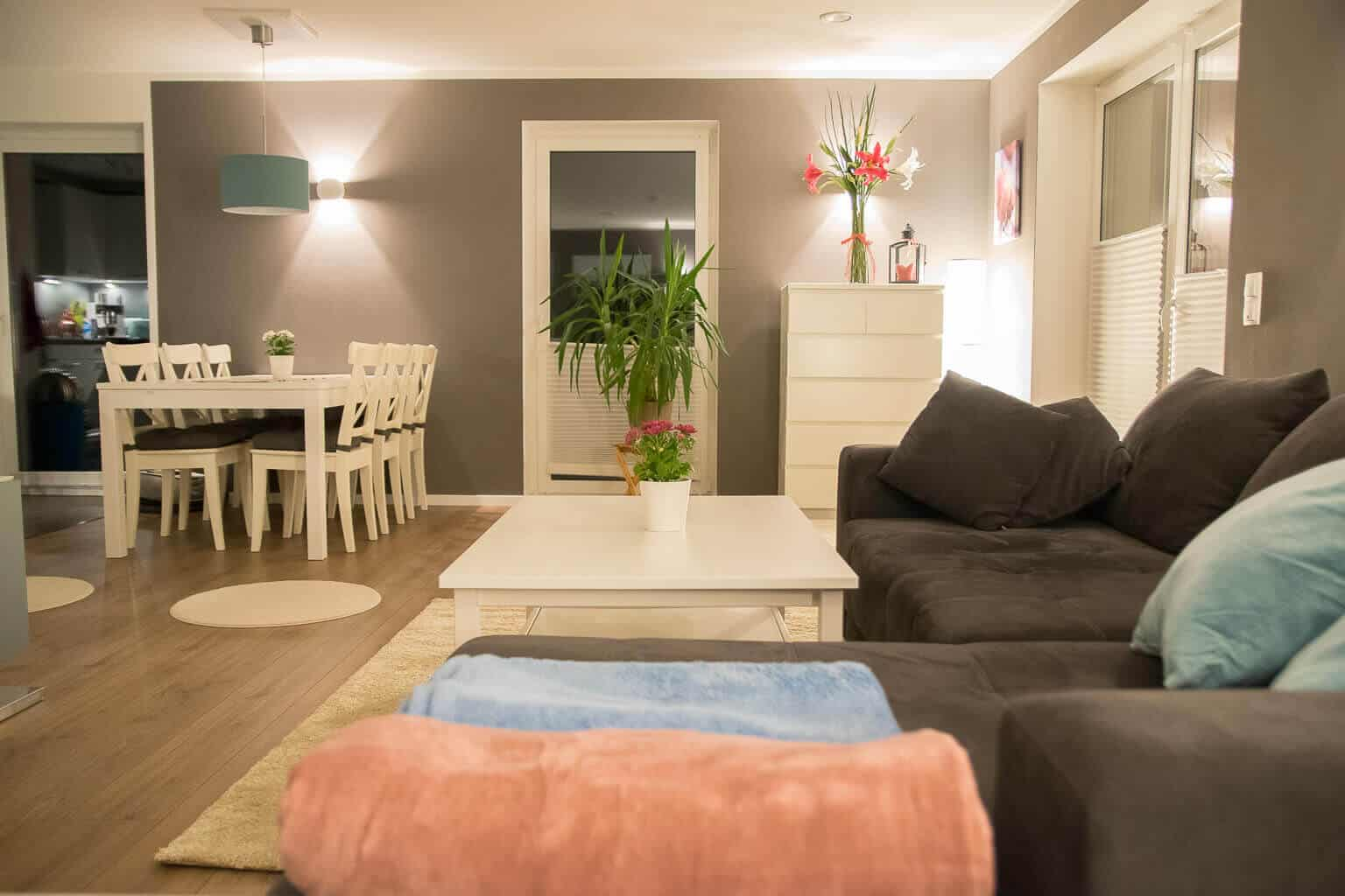 Graue Wände im Wohnzimmer mit hellen Möbeln und bunten Decken