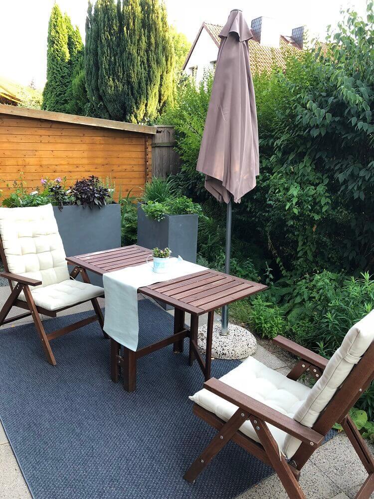 kleine sitzecke mit outdoorteppich und sonnenschutz