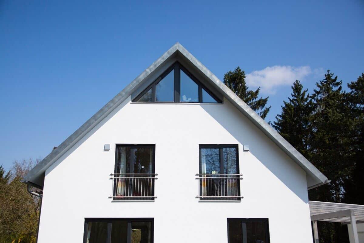Ein freistehendes Einfamilienhaus mit Satteldach und weiße Fassade