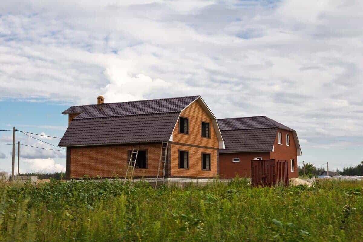 Zwei Einfamilienhäuser mit Mansarddächern, das hintere Haus verfügt zusätzlich über ein Krüppelwalm