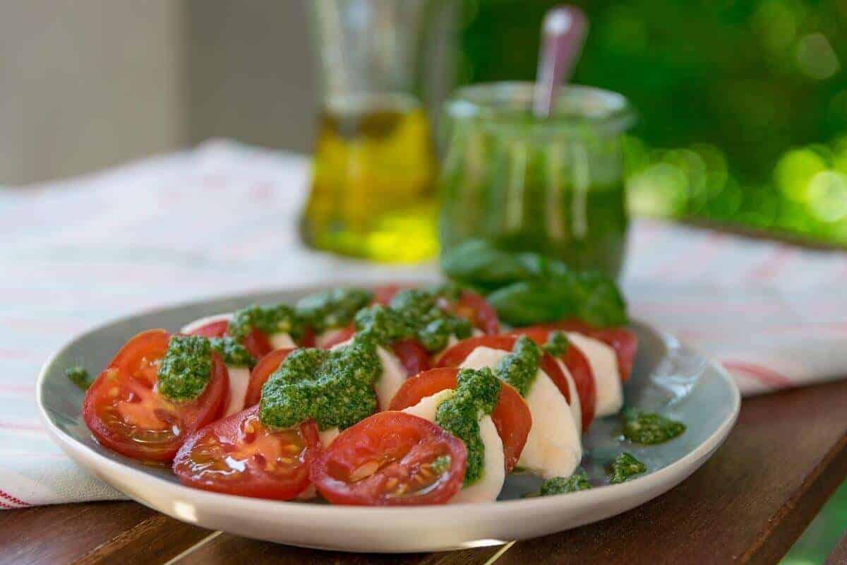 Basilikum Pesto auf Tomate Mozzarella schmeckt selbstgemacht mit frischen Kräutern am Besten
