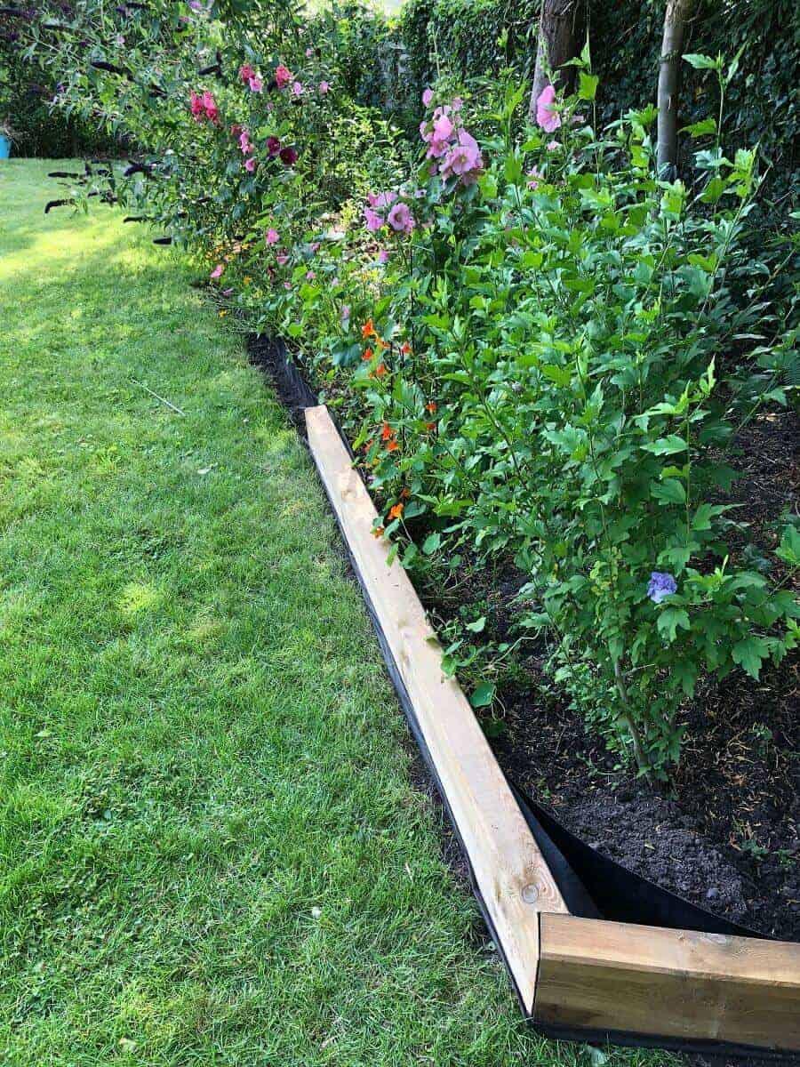 Die Beeteinfassung nimmt Formen an, wir legen die Gartenschwellen entlang der Bambussperre, damit diese nicht mehr sichtbar ist