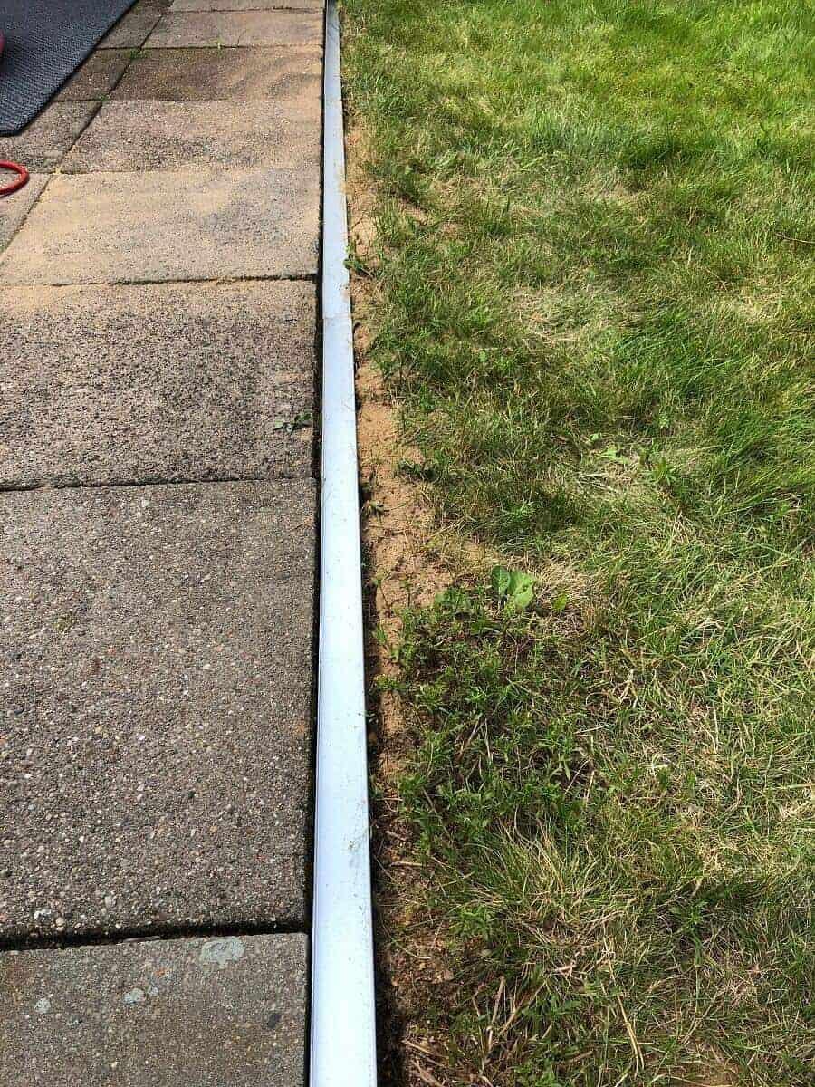 Die Rasenkante aus Metall ist frisch eingebaut, nun muss mit Sand und Erde aufgefüllt werden