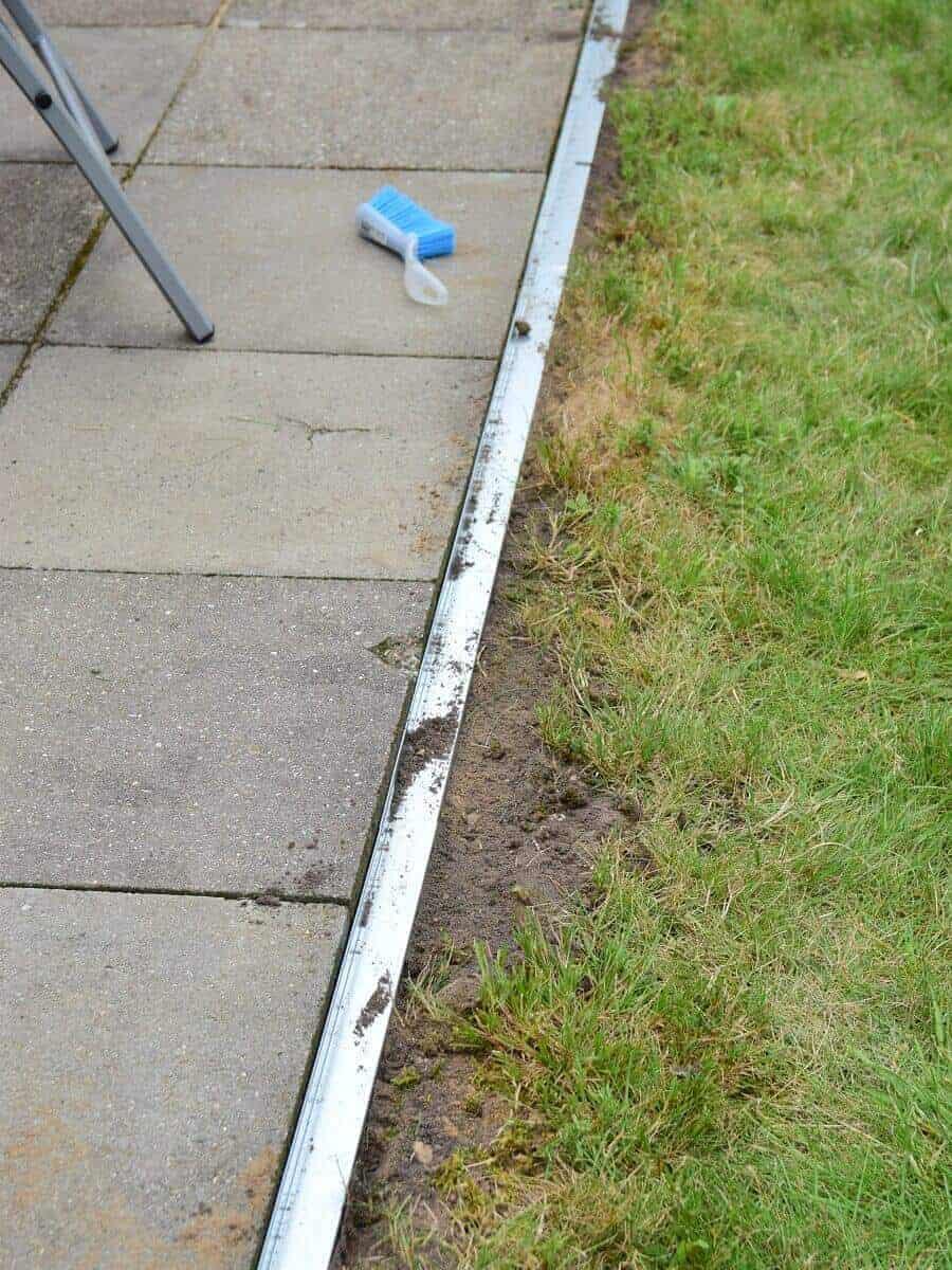 Die Rasenkante mit Radlauf aus Metall an der Terrasse ist fertig verlegt