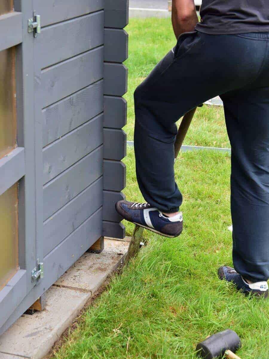 Mit dem Spaten wird ein kleiner Spalt in den Boden gebracht, damit dort die Rasenkante eingesetzt werden kann
