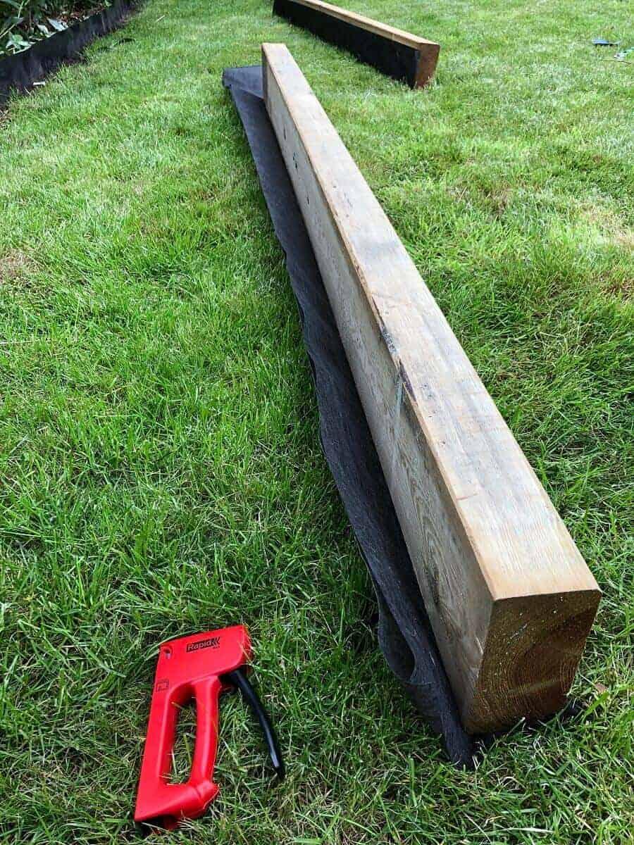 Wir haben Unkrautvlies an den Gartenschwellen und an der Bambussperre befestigt, damit dazwischen kein Unkraut wächst