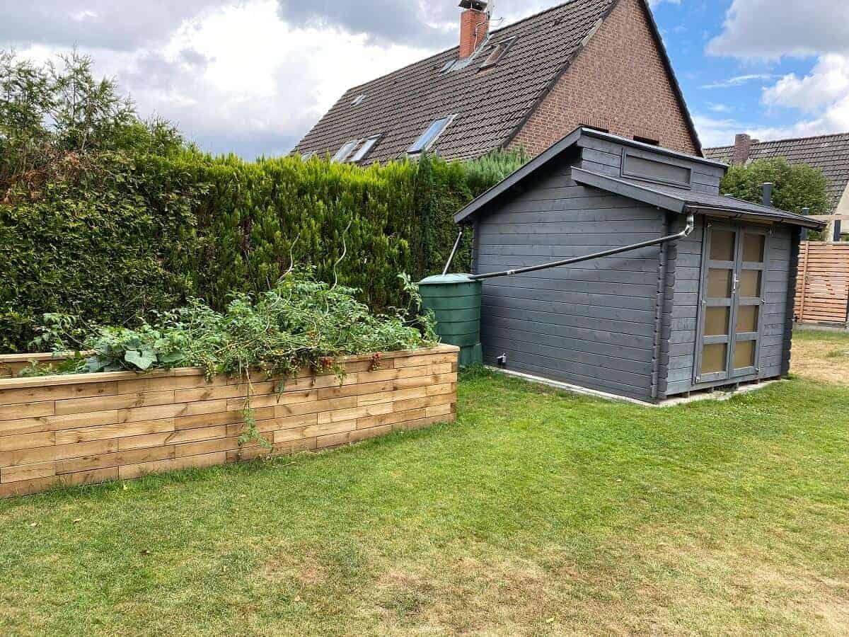 wir haben die regenwassertonne hinter dem gartenhaus versteckt und nutzen das aufgefangene regenwasser unter anderem für unser hochbeet